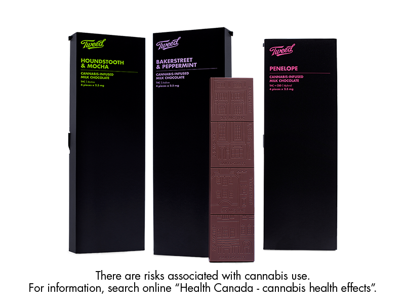 Three cannabis-infused chocolate bars standing vertically with one unwrapped bar